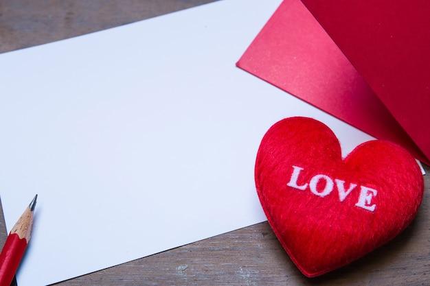 Envolvente roja con almohada de corazón de forma sobre amor de texto, hoja de papel y sobre fondo de madera