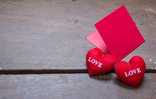 Envolvente roja con almohada de corazón de forma sobre el amor de texto y sobre fondo de madera