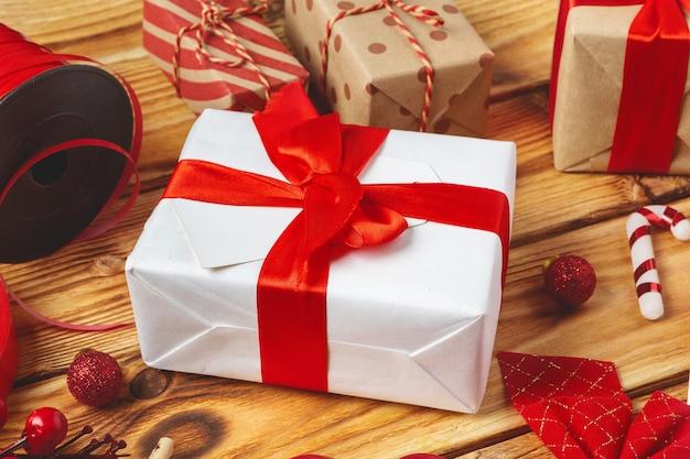 Envolver cajas de regalo con equipos y artículos de decoración sobre fondo de madera