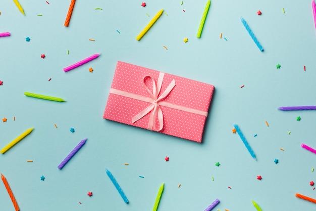 Envuelto caja de regalo alrededor de las velas de colores y asperja sobre fondo azul