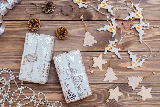 Envuelto en cajas de regalo festivas atadas con cinta de plata y adornos navideños en una mesa de madera. preparándose para la navidad.