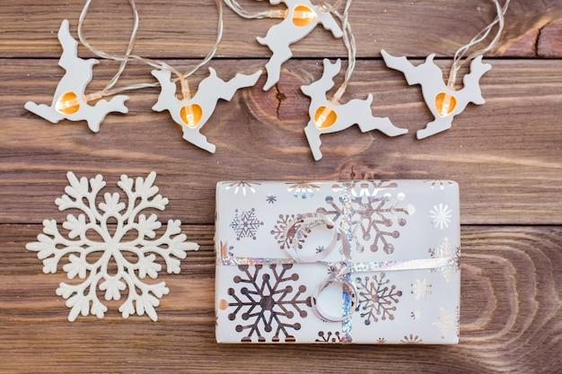 Envuelto en cajas de regalo festivas atadas con cinta de plata, copo de nieve y guirnalda de ciervos de navidad en una mesa de madera. preparándose para la navidad.