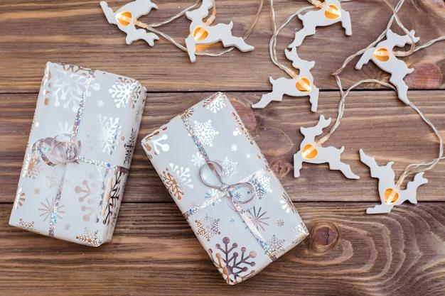 Envuelto en cajas de regalo festivas atadas con cinta de plata y guirnalda de ciervos de navidad en una mesa de madera. preparándose para la navidad.