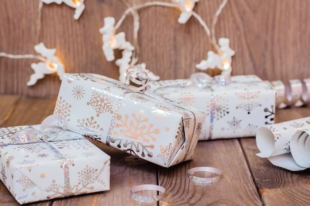 Envuelto en cajas de regalo festivas atadas con una cinta de plata, un rollo de papel de regalo y adornos navideños en una mesa de madera. preparándose para la navidad.