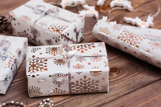 Envuelto en cajas de regalo festivas atadas con cinta de plata y un rollo de papel de regalo sobre una mesa de madera. preparándose para la navidad.