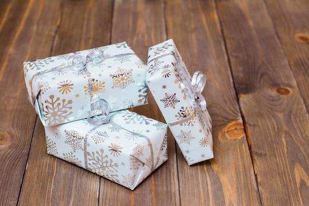 Envuelto en cajas de regalo festivas atadas con cinta de plata sobre una mesa de madera. preparándose para la navidad.