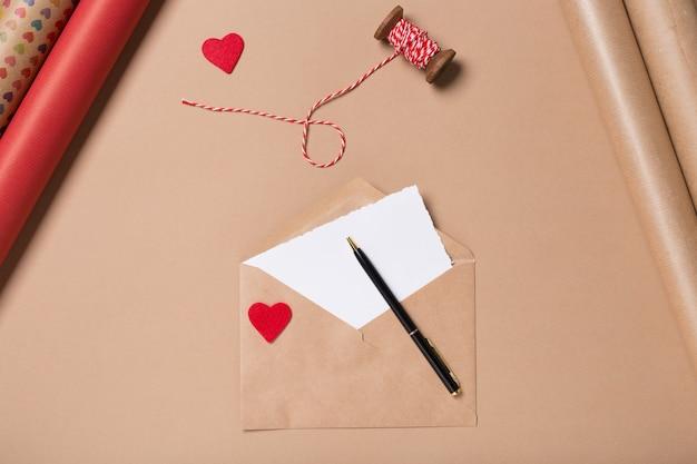 Envuelva el sobre con el corazón rojo, el papel en blanco y la pluma en la tabla beige. envase. concepto de amor dia de san valentin