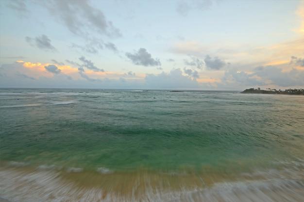 Épica puesta de sol playa tropical en sri lanka, cielo dramático nubes monzónicas