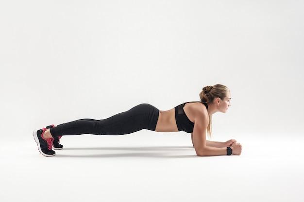 Equilibrio y concentración. fuerte mujer rubia de pie en la plancha. tiro del estudio