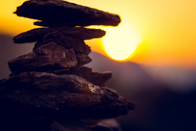 Equilibrio de piedras de spa, cielo de verano colorido, silueta de piedras y mariposas apiladas, hermosa naturaleza, pacífica puesta de sol en la playa, imagen actual de vida estable