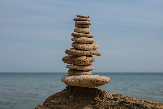 Equilibrio de pirámide de piedras en una gran piedra en la orilla del mar