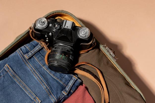 Equipaje abierto con ropa doblada y cámara