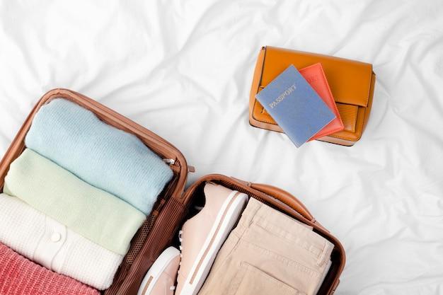 Equipaje abierto con ropa doblada y pasaporte.
