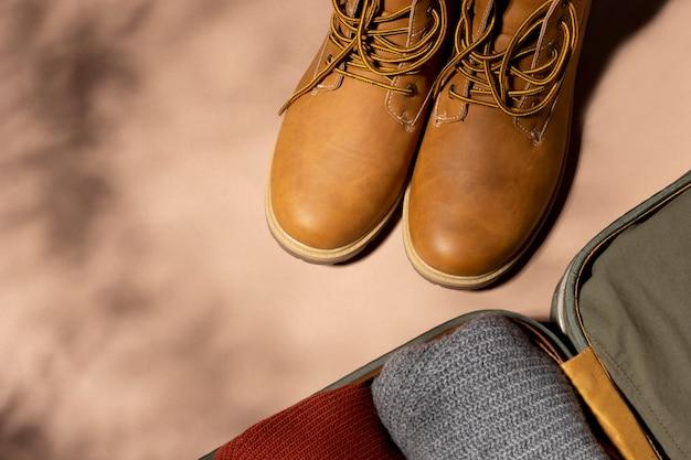 Equipaje abierto con ropa doblada y zapatos.