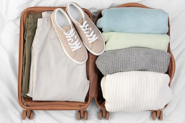 Equipaje abierto con ropa y zapatos doblados.