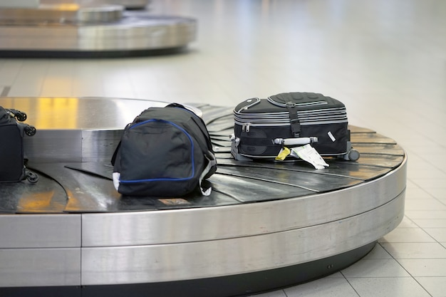 Equipaje en cinta transportadora en el aeropuerto. área de reclamo de equipaje en el aeropuerto, línea de equipaje abstracta con muchas maletas.