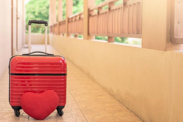 Equipaje rojo con corazón rojo en borroso para actividad estilo de vida al aire libre