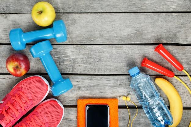 Equipamiento deportivo y el teléfono inteligente con auriculares en madera