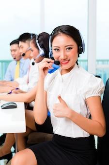 Equipo de agente de centro de llamadas asiático asiático en el teléfono