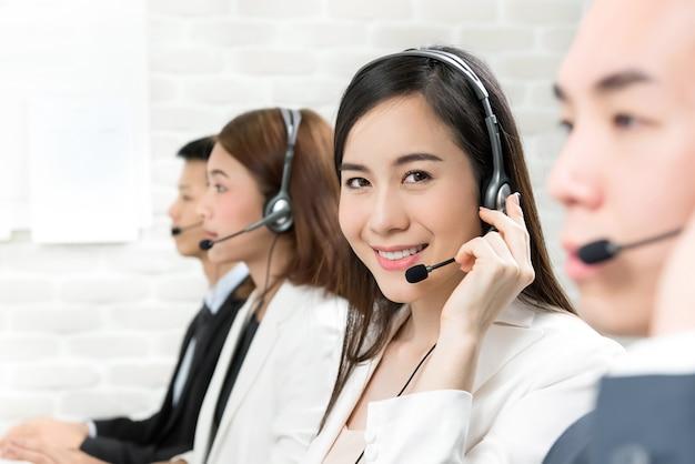Equipo de agente de servicio al cliente de telemarketing asiático que trabaja en call center