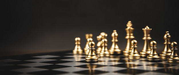 El equipo de ajedrez dorado de pie sobre el tablero de ajedrez