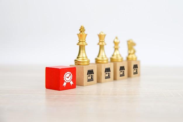 Equipo de ajedrez de pie sobre la pila de bloques de madera con el icono de la tienda de negocios de franquicias.