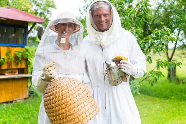 Equipo de apicultores trabajando al aire libre con ahumador y colmena.