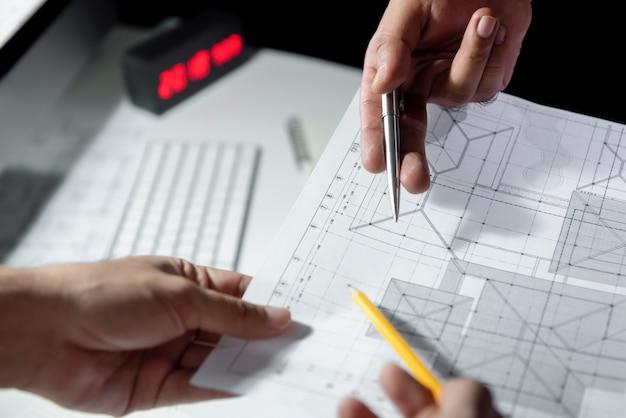 Equipo del arquitecto que discute el papel de modelo en oficina