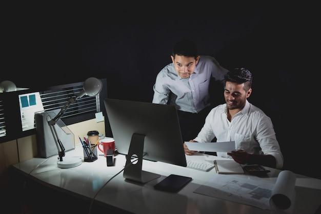 Equipo de arquitectos asiáticos trabajando en la noche