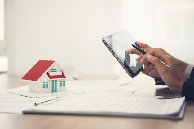 Equipo de arquitectos discutiendo planos de planta y casa modelo usando tableta