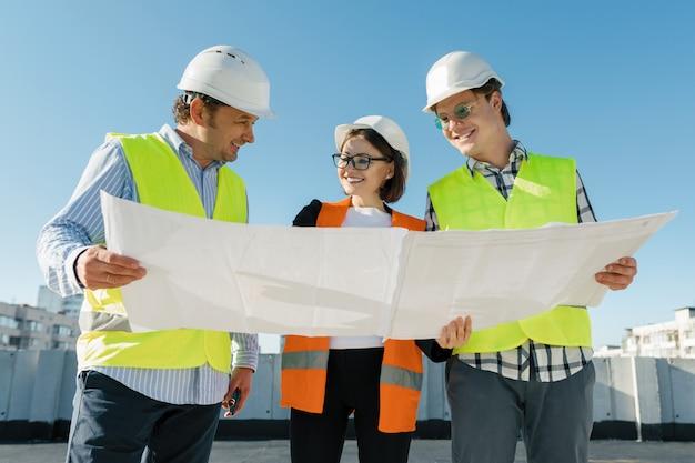 El equipo de arquitectos del ingeniero de los constructores en el tejado del emplazamiento de la obra.