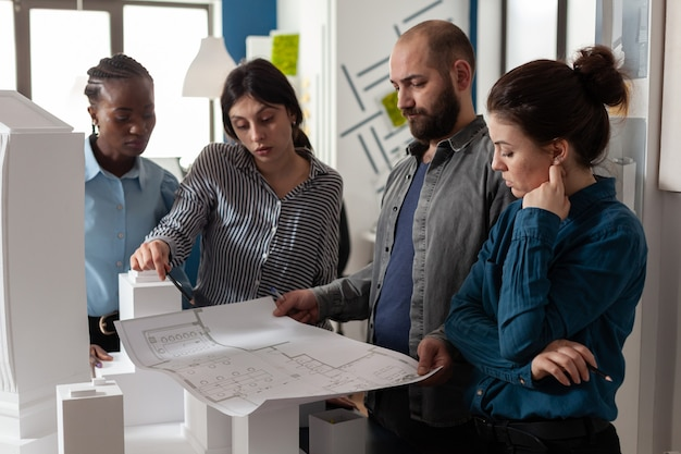 Equipo de arquitectos multiétnicos que diseñan el plan de planos