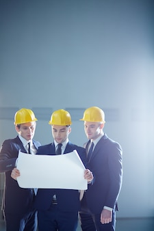 Equipo de arquitectos trabajando en planos de construcción