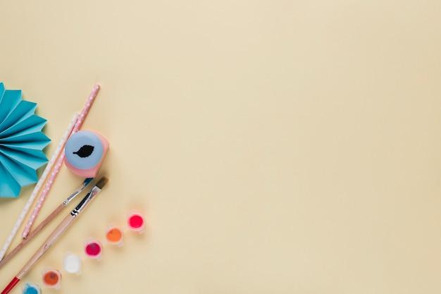 Equipo artesanal y abanico de papel de origami azul sobre fondo beige