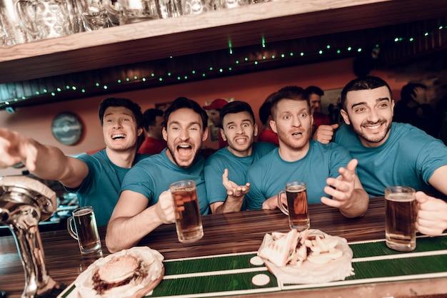 Equipo azul fanáticos de los deportes en el bar bebiendo cerveza.