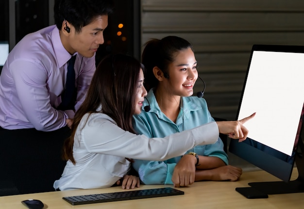 Equipo de call center trabajando juntos por la noche