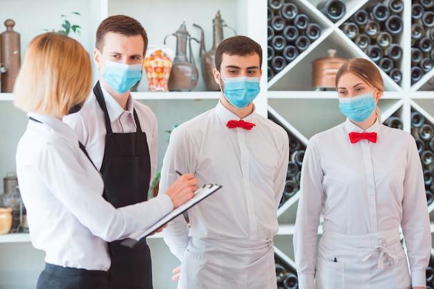 Un equipo de camareros realiza una sesión informativa en la terraza de verano del restaurante.