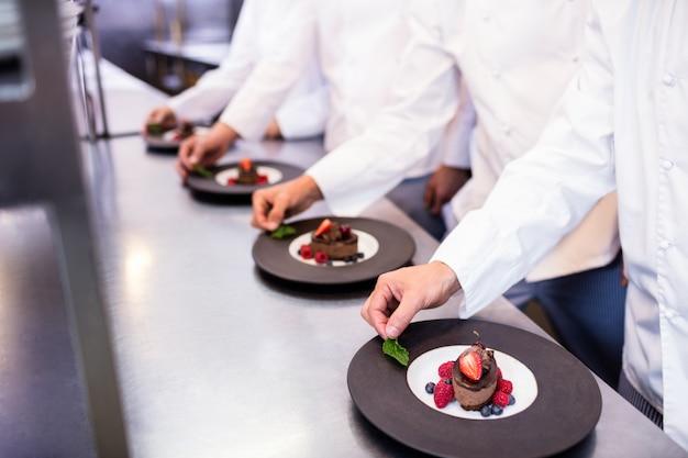Equipo de chefs terminando platos de postre en la cocina.