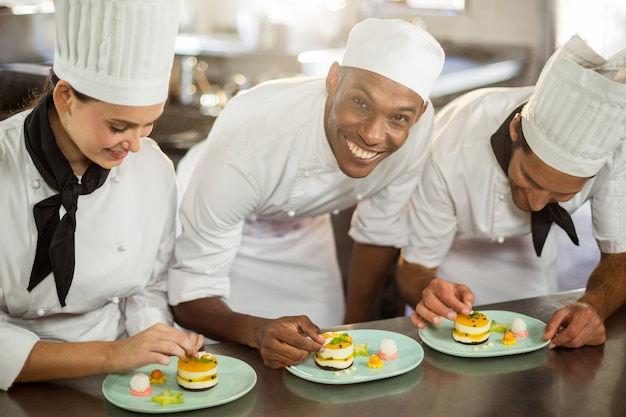 Equipo de chefs terminando platos de postre