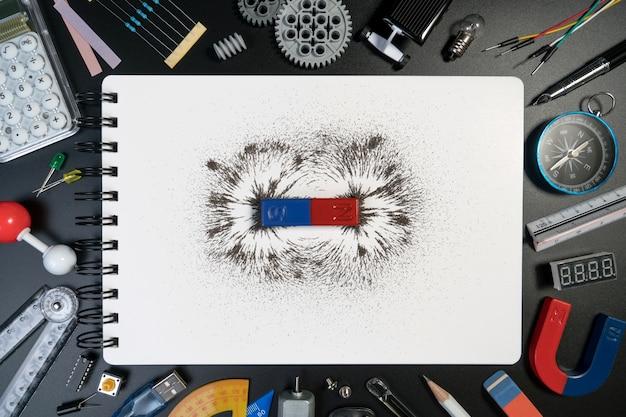 Equipo de ciencia, accesorios y barra magnética campo magnético en el cuaderno blanco.