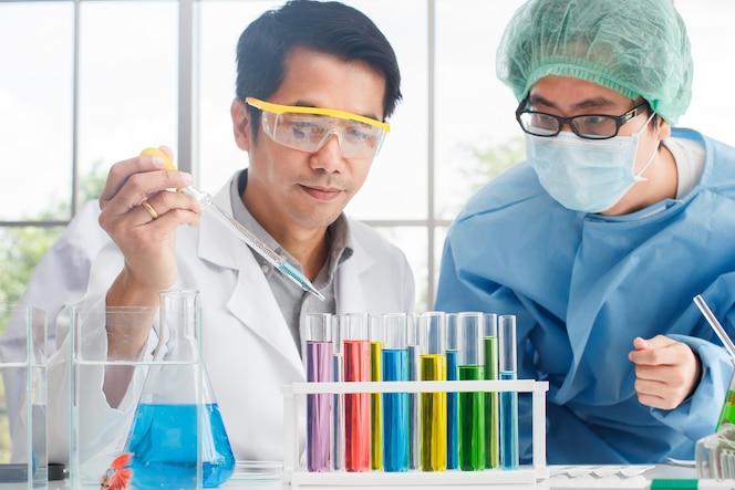 Equipo científico masculino que trabaja con el tubo de ensayo del vaso de precipitados del color