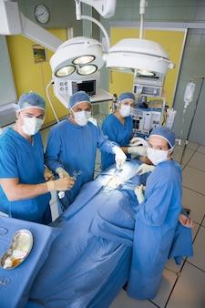 Equipo de cirugía mirando la cámara durante la operación.