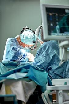 Equipo de cirujanos para trabajar en quirófano. varios cirujanos están haciendo una operación en una sala de operaciones real. luz azul, guantes blancos tiro vertical.