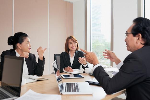 Equipo de colegas discutiendo asuntos corporativos en la sesión de lluvia de ideas