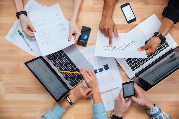 Equipo de colegas que trabajan para informes financieros utilizando computadoras portátiles y teléfonos inteligentes.