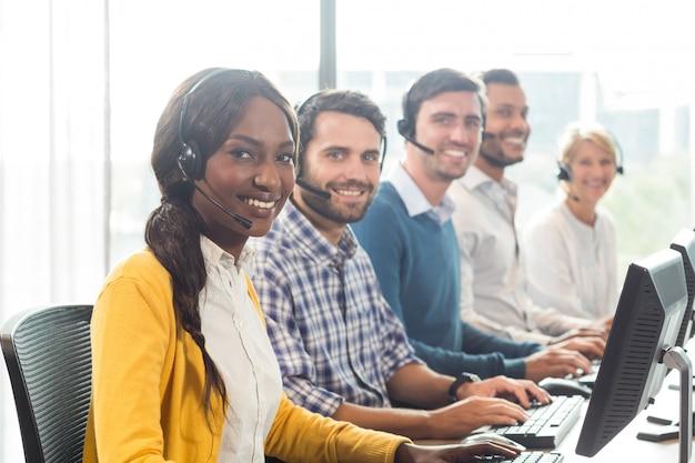 Equipo de colegas que trabajan en su escritorio con auriculares