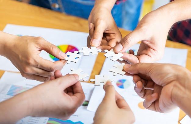 Equipo colocando cuatro rompecabezas rompecabezas juntos para el concepto de equipo