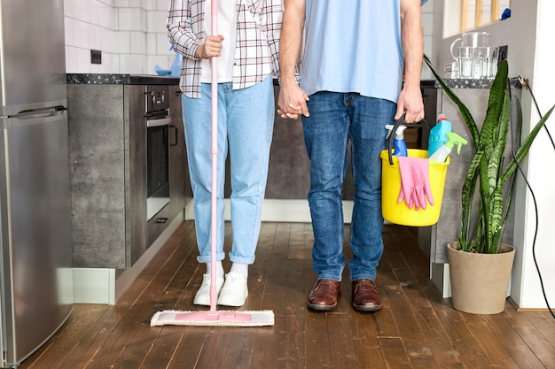 El equipo de conserjes recortó al hombre y a la mujer en ropa casual con productos de limpieza en las manos posando en casa