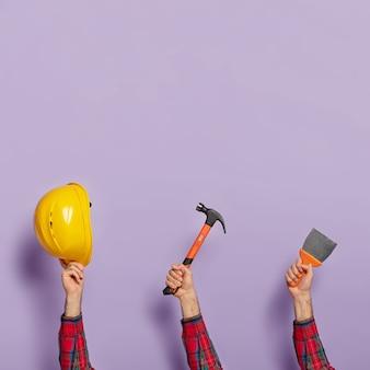 Equipo de construcción contra la pared púrpura