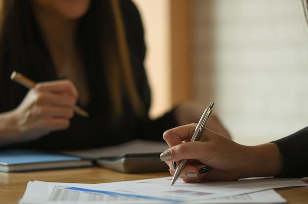 El equipo contable femenino está analizando los datos para resumir el presupuesto.